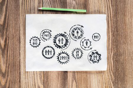 Foto de Corporate social responsibility concept with group of rotating gears and cogs. Human resources cooperation sketch on wooden surface. Workplace with paper and pencil lying on wooden desk. - Imagen libre de derechos