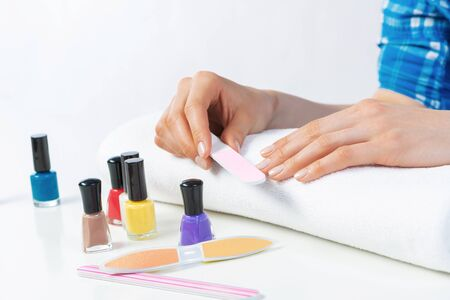 Photo for Woman using nail file and create perfect nails shape. Colorful nail polish bottles on table. Grinding female nails with nail file. Woman doing herself nail care procedure at home. Beauty and hygiene - Royalty Free Image