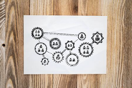 Foto de Human resource recruitment pencil hand drawn with group of rotating cogwheels. Headhunting and team building sketch on wooden surface. Top view of workplace with sheet of paper lying on wooden desk. - Imagen libre de derechos