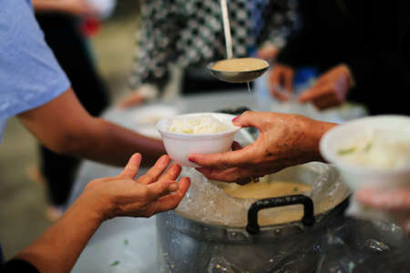 Foto de Feeding the poor to hands of a beggar. Poverty concept - Imagen libre de derechos