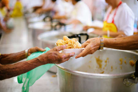Foto de Homeless people are helped with food relief, famine relief : a social concept of sharing. - Imagen libre de derechos