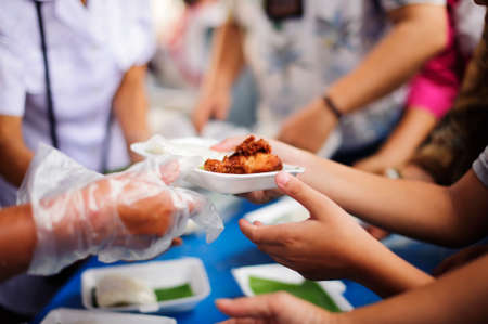 Photo pour Volunteers provide food for beggars : Concepts Feeding and help : Concept of food sharing for the poor to alleviate hunger : Volunteers Share Food to the Poor - image libre de droit