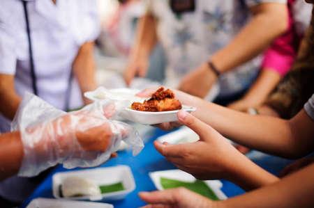 Foto de Volunteers provide food for beggars : Concepts Feeding and help : Concept of food sharing for the poor to alleviate hunger : Volunteers Share Food to the Poor - Imagen libre de derechos
