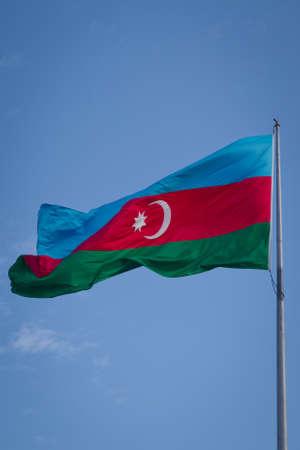 Foto de Successful silhouette man winner waving Azerbaijan flag on top of the mountain peak. Azerbaijan flag waving in the wind against cloudy sky - Imagen libre de derechos