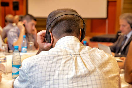 Photo for People using ear headphones for translation during event and meeting - Royalty Free Image