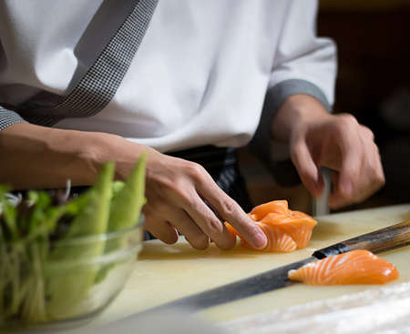 Foto de Chef Japanese cuisine in hotel or restaurant kitchen cooking, only hands. He is working sushi - Imagen libre de derechos