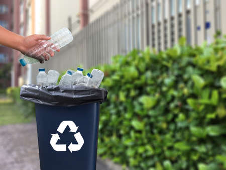 Foto de Man's hand putting plastic reuse for recycling concept environmental protection world recycle - Imagen libre de derechos