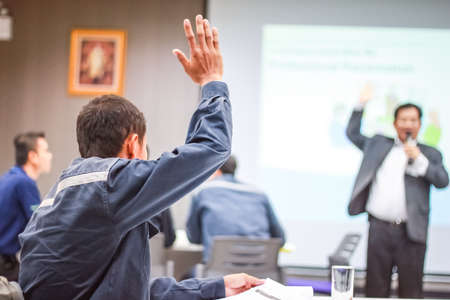 Photo for Students lifting hands in college class with teacher - Royalty Free Image