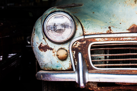 Photo pour Detail of the front headlight of an old car in garage - image libre de droit