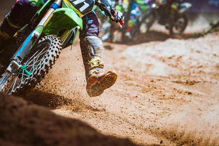 Photo for Close-up part of mountain bikes race in dirt track with flying debris during an acceleration in sunshine day time. Concept of focus between an accelerate in action sport - Royalty Free Image