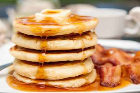 Photo for A tall stack of pancakes with butter and dripping syrup and three strips of bacon - Royalty Free Image