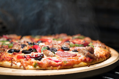 Photo pour Hot supreme thin crust pizza cooking in oven with steam and smoke - image libre de droit