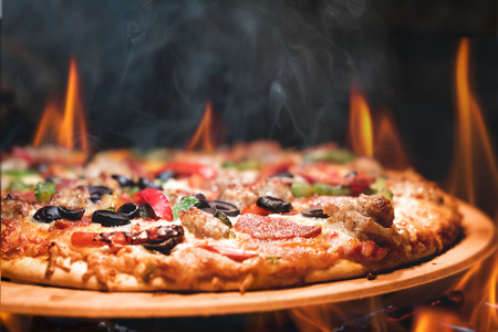 Foto de Supreme meat and vegetable pizza on stone in wood-fired oven with open flames - Imagen libre de derechos