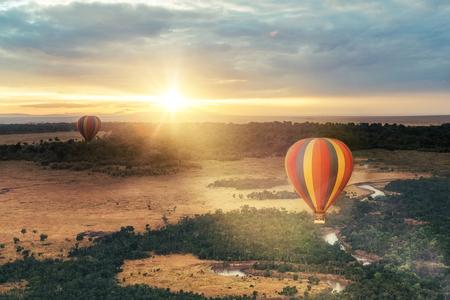 Foto de Beautiful aerial view of colorful hot air balloons floating over the Masai Mara National Reserve at golden sunrise - Imagen libre de derechos