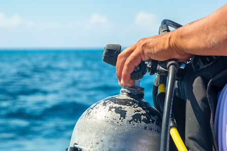 Photo pour Closeup of the hand of a scuba diver on the nozzle of an oxygen tank on a boat with ocean water in background - image libre de droit