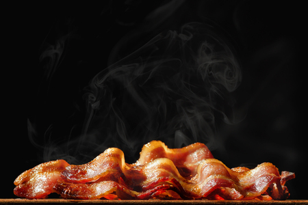 Photo for Pile of steaming hot freshly cooked bacon with room for text in black background - Royalty Free Image