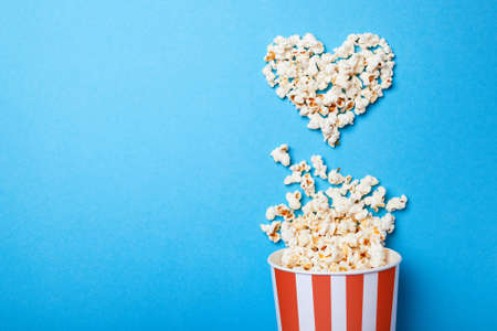 Foto de I like watching films. Spilled popcorn in the shape of heart and paper bucket in a red strip on blue background. Copy space for text - Imagen libre de derechos