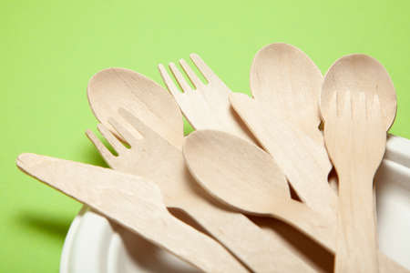 Photo for Eco-friendly disposable utensils made of bamboo wood and paper on a green background. Draped spoons, fork, knives, bamboo bowls - Royalty Free Image