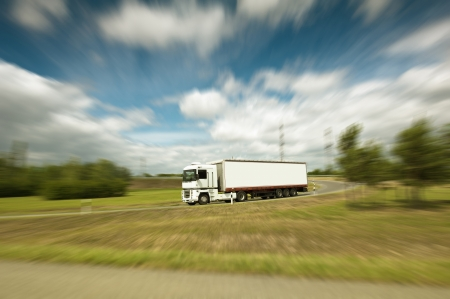 Photo pour White truck on blurry asphalt under blue sky with clouds  - image libre de droit