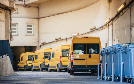 Photo pour Row of yellow delivery and service van, trucks and cars in front of the entrance of a warehouse distribution logistic plant - image libre de droit