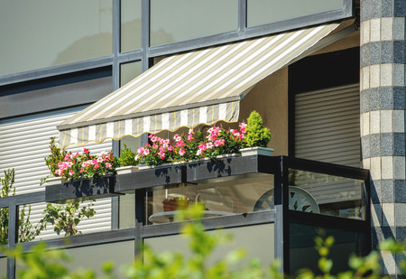 Foto de Balcony with awning opened and beautiful flowers - covered by sun-shield on a warm summer day - Imagen libre de derechos