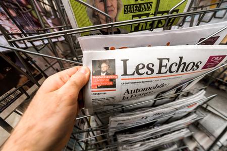 Foto de PARIS, FRANCE - MAR 15, 2018: POV man holding Les Echos newspaper with Stephen Hawking portrait - Imagen libre de derechos