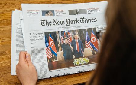 Foto de PARIS, FRANCE - JUNE 13, 2018: Woman reading The New York Times newspaper in the office showing on cover  U.S. President Donald Trump meeting North Korean leader Kim Jong-un in Singapore - Imagen libre de derechos