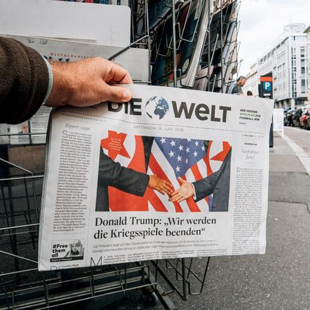 Foto de PARIS, FRANCE - JUNE 13, 2018: Square image of Man buying The Daily Telegrph newspaper at press kiosk showing on cover  U.S. President Donald Trump meeting North Korean leader Kim Jong-un in Singapore - Imagen libre de derechos