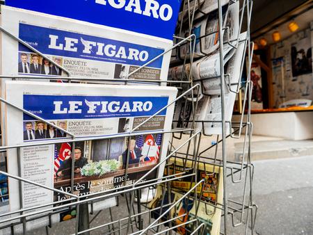Foto de PARIS, FRANCE - JUNE 13, 2018: Man buying Le Figaro newspaper at press kiosk showing on cover  U.S. President Donald Trump meeting North Korean leader Kim Jong-un in Singapore - Imagen libre de derechos