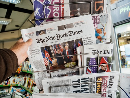 Foto de PARIS, FRANCE - JUNE 13, 2018: Man buying The New York Times newspaper at press kiosk showing on cover  U.S. President Donald Trump meeting North Korean leader Kim Jong-un in Singapore - Imagen libre de derechos