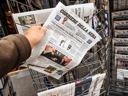 Foto de PARIS, FRANCE - JUNE 13, 2018: Man buying Corriere della sera newspaper at press kiosk showing on cover  U.S. President Donald Trump meeting North Korean leader Kim Jong-un in Singapore - Imagen libre de derechos