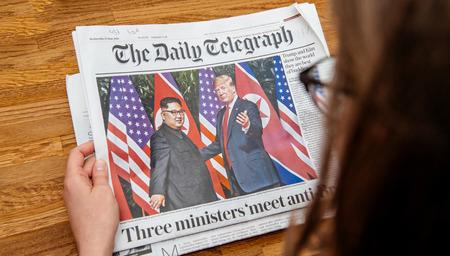 Foto de PARIS, FRANCE - JUNE 13, 2018: Woman reading The Daily Telegrpah newspaper in the office showing on cover  U.S. President Donald Trump meeting North Korean leader Kim Jong-un in Singapore - Imagen libre de derechos