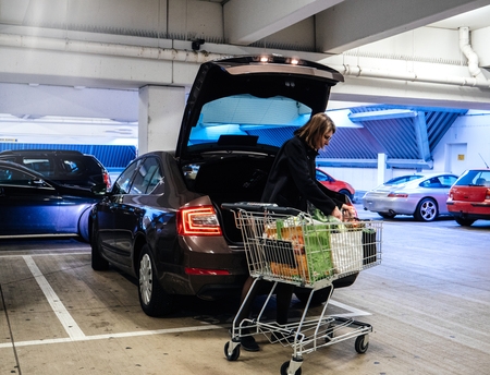 Foto de Side view of woman with shopping trolley near car putting bags with groceries into trunk on parking lot - Imagen libre de derechos