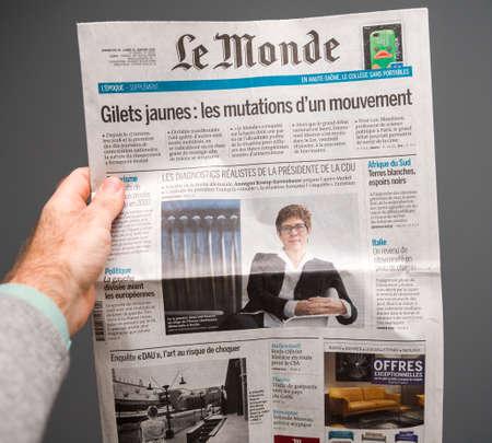 Foto de Paris, France - Feb 22, 2019: Man hand holding against gray background Le Monde newspaper with portrait of Annegret Kramp-Karrenbauer and article about Yellow vests protest - Imagen libre de derechos