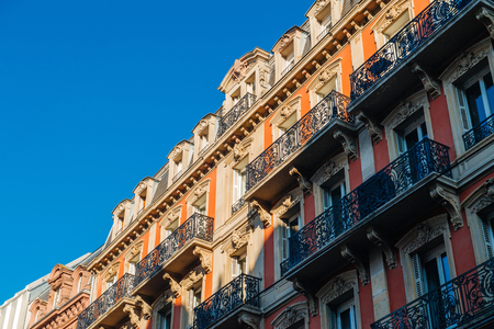 Foto de Majestic balconies view from below of French Haussmannian apartment building with clear blue sky early in the morning - real estate property management luxury in France - Imagen libre de derechos