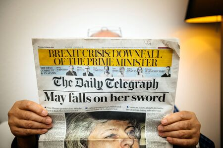 Foto de Paris, France - 29 Mar 2019: Senior man reading in living room latest british The Daily Telegraph newspaper UK press featuring Theresa may PM on front cover - Imagen libre de derechos
