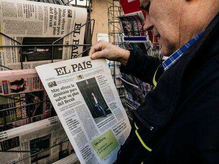 Foto de Paris, France - 29 Mar 2019: Newspaper stand kiosk selling press with senior male hand buying latest Spanish El Pais featuring Brexit news on front cover - Imagen libre de derechos