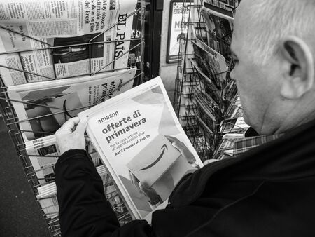 Foto de Paris, France - 29 Mar 2019: Newspaper stand kiosk selling press with senior male hand buying latest italian press featuring Amazon Oferta di Primavera spring offer on front cover black and white - Imagen libre de derechos