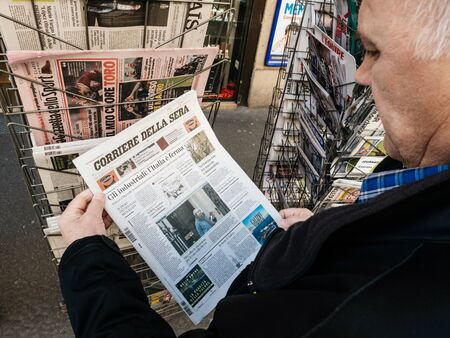 Foto de Paris, France - 29 Mar 2019: Newspaper stand kiosk selling press with senior male hand buying latest Italian Corriere della sera featuring Theresa May on front cover Brexit - Imagen libre de derechos