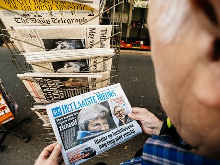 Foto de Paris, France - 29 Mar 2019: Newspaper stand kiosk selling press with senior male hand buying latest Het Laatste Nieuws dutch press featuring Theresa May Prime Minister Brexit news on front cover - Imagen libre de derechos
