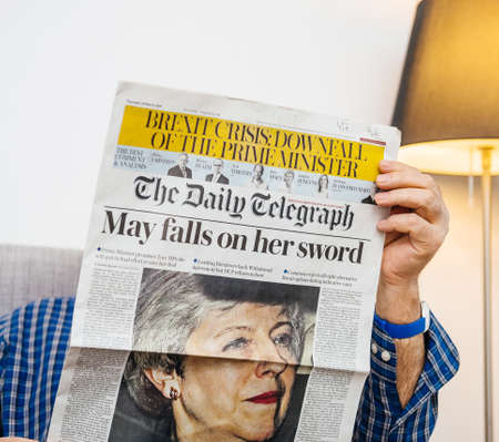Foto de Paris, France - 29 Mar 2019: man reading in living room latest british The Daily Telegraph newspaper UK press featuring Theresa may PM on front cover - Imagen libre de derechos