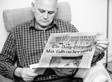 Foto de Paris, France - 29 Mar 2019: Black and white image senior man reading in living room latest british The Daily Telegraph newspaper UK press featuring Theresa may PM on front cover - Imagen libre de derechos