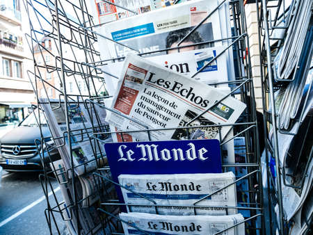 Foto de Paris, France - 29 Mar 2019: Newspaper stand kiosk selling press with senior male hand buying latest featuring  on front cover - Imagen libre de derechos