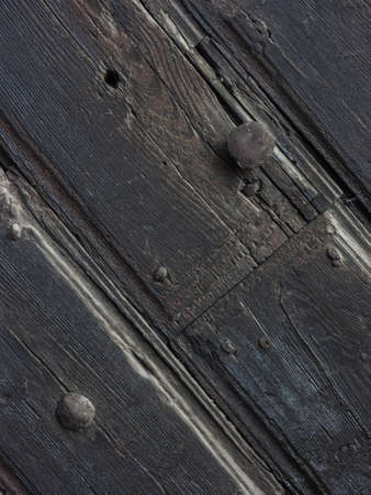Photo for Antique door with wooden plank panels of a rural house, with iron fixing parts, Italy. - Royalty Free Image