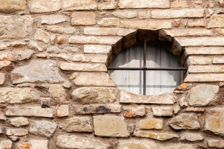 Photo for Typical detail of an old wall of an Italian house with a circular window, made of hand-carved stones eroded by time. - Royalty Free Image