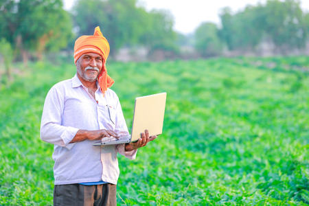 Photo pour Indian rural farmer using laptop - image libre de droit
