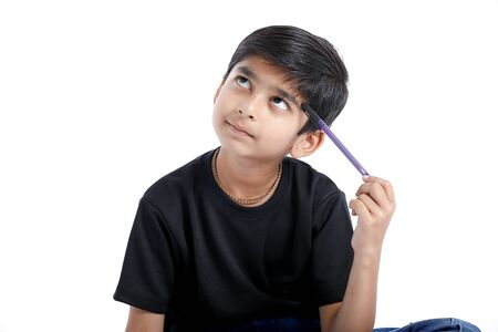 Foto de Cute Indian boy thinking idea and looking at up, isolated on white background - Imagen libre de derechos