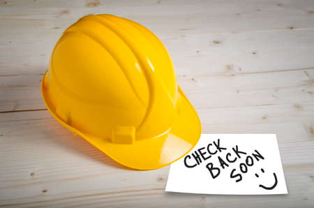Photo for Check back soon note on paper on wooden background with safety helmet. - Royalty Free Image