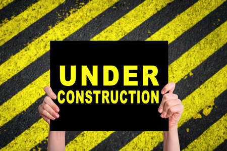 Foto de Under Construction card with safety stripes on construction site. - Imagen libre de derechos