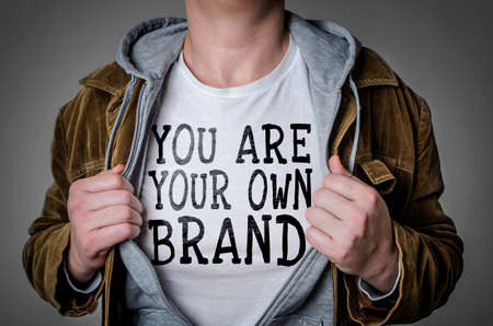 Foto de Man showing You Are Your Own Brand tittle on t-shirt. Personal branding concept. - Imagen libre de derechos